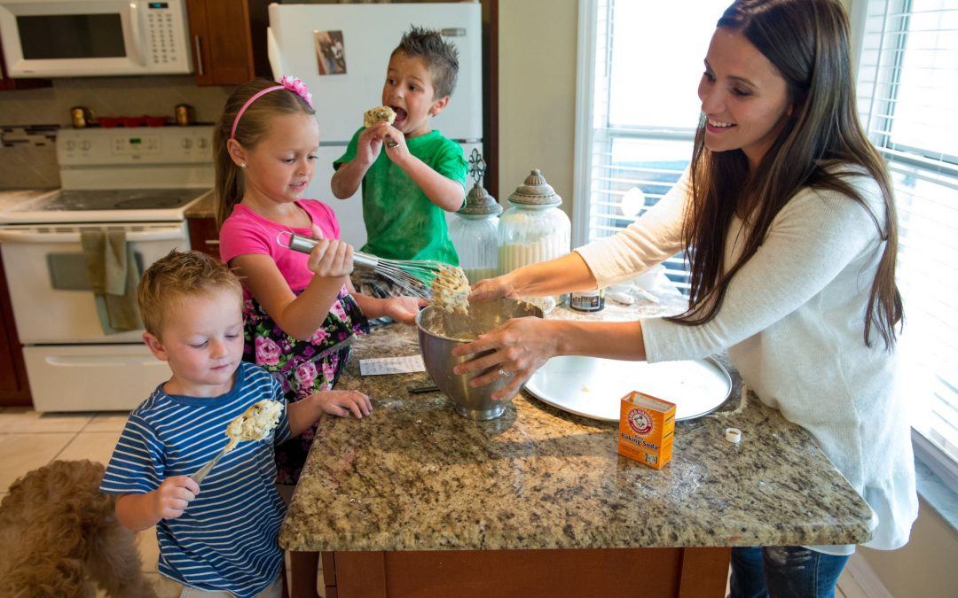 A mom is baking with her children in the kitchen.