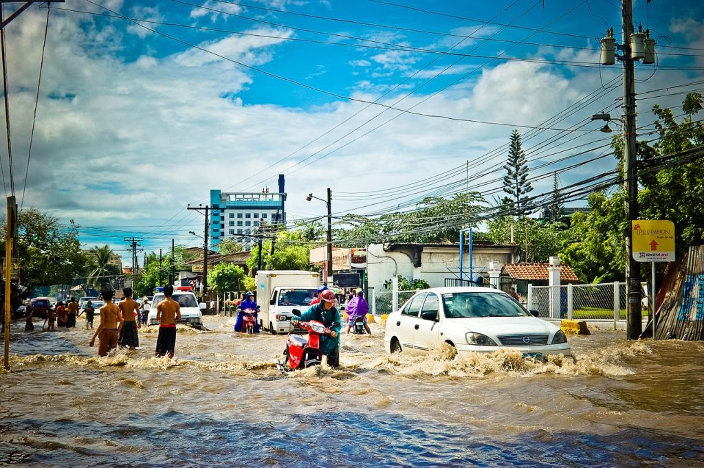 People wading through a flooded street. Prophecies concerning the last days warn of flooding and other natural disasters.